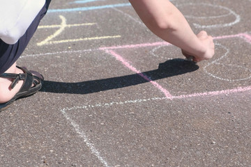 Woman draws a hopscotch on the asphalt with colorful chalks. Close-up hand.