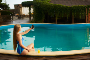 Attractive blonde woman with long hair sitting at poolside and taking selfie portrait with cellphone camera. Slim girl wear blue striped body swimsuit and holds a glass with orange juice.