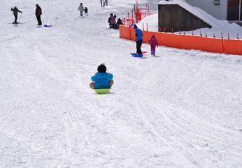 スキー場でそり遊びをする子供たち