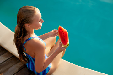 Pretty woman holds slice red watermelon stretching long tanned legs over blue pool, relaxing on tropical island in resort, eating healthy food. Fruit summer diet. Vegetarianism and vegan lifestyle.