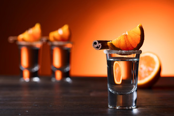 Glasses of tequila with orange and cinnamon.