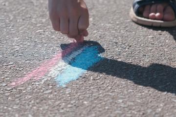 Boy draws with blue chalk on the asphalt. Close-up hands.