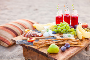Photo sur Aluminium Pique-nique Picnic on the beach at sunset in the style of boho. Concept outdoors evening healthy dinnner with fruit and juice