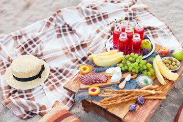 Deurstickers Picknick Picnic on the beach at sunset in the style of boho. Concept outdoors evening healthy dinnner with fruit and juice