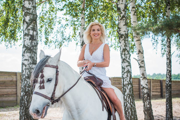 Beautiful american girl with a horse in the nature. Concept of horse and human. Portrait of young artistic woman walking with horse outdoors