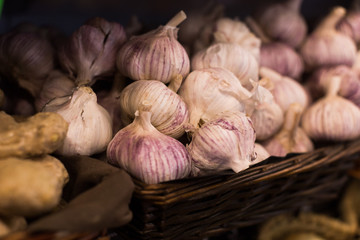heads of fragrant garlic in baskets on market counter