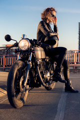 Sexy biker woman in black leather jacket sit on vintage custom caferacer motorcycle and correct sunglasses. Urban roof parking, sunset in big city. Traveling and active hipster lifestyle. Girls power.