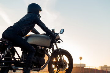 Sexy biker female in black leather jacket and full face helmet sit on vintage custom caferacer motorcycle. Urban roof parking, sunset in big city. Traveling and active hipster lifestyle. Girls power.