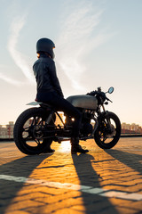 Sexy biker female in black leather jacket and full face helmet sit on vintage custom caferacer motorbike. Urban roof parking, sunset in big city. Traveling and active hipster lifestyle. Girls power.