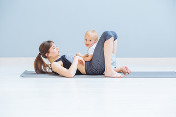 Sportive brunette mother workout together with hungry toddler baby wtih stick out tongue child wantins to breastfeeding. Fitness, happy maternity and weaning concept.