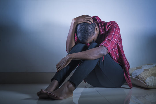 lifestyle indoors portrait of young sad and depressed black african American woman sitting at home floor feeling desperate and worried suffering pain