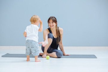 Happy todler boy giving high five to his laughing sportive mother. Fitness, happy maternity yoga with children concept.