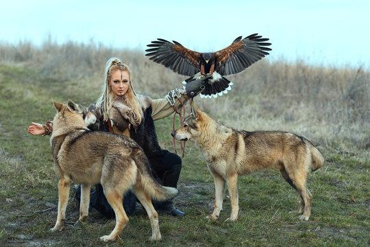 Beautiful northern warrior viking woman with traditional makeup with wolves and Harris Hawk (Parabuteo unicinctus). Viking woman training her predators.