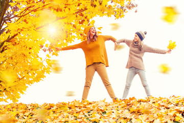 mother and daughter have fun in autumn october golden