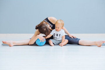 Sport, motherhood and active lifestyle concept - mother stretching legs together with her toddler boy over gray wall background. Mom having fun and playing blue ball with her little son.