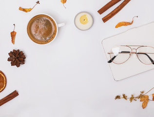 Autumn flat lay with coffee, candle and yellow leaves