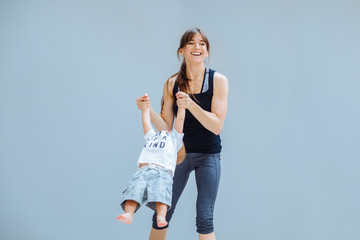 Happy laughing mother doing gymnastic for toddler baby boy over gray background at home. Fitness, happy maternity yoga with children concept.