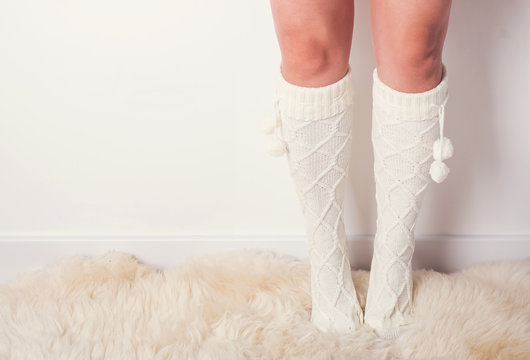 Woman's legs in socks standing on fur carpet