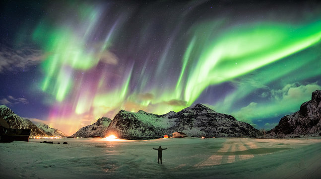 Aurora borealis (Northern lights) over mountain with one person
