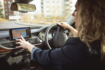 Female executive using navigation while driving a car