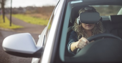 Female executive using virtual reality headset while driving a