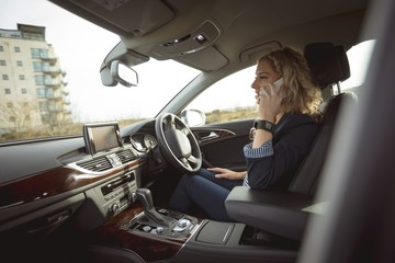 Female executive talking on mobile phone in a car