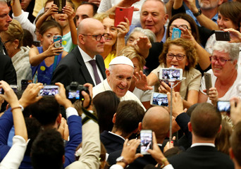 Pope Francis is greeted by faithful as he arrives to lead the general audience at the Paul VI Hall in Vatican