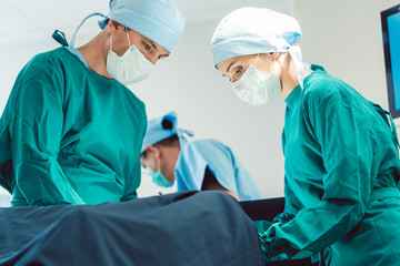Doctors and surgeons operating patient in hospital with full concentration