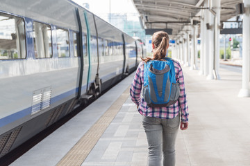 Young female tourist walking along platform to catch train