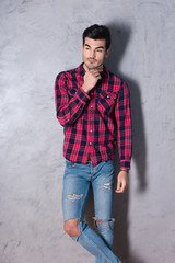 A thinking handsome young man in a red checkered shirt standing in front of a grey wall in a studio.