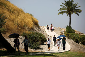 Visitors walk next to the Tel Megiddo Archaeological site