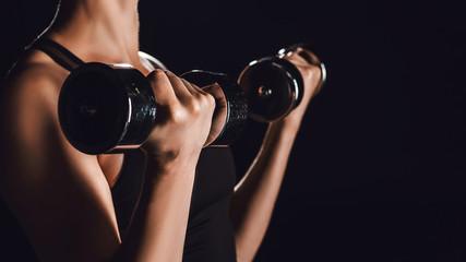 cropped image of female athlete exercising with dumbbells, black background