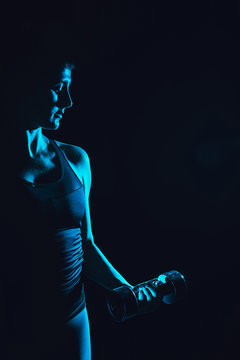 toned picture of sportswoman doing exercise with dumbbell, black background