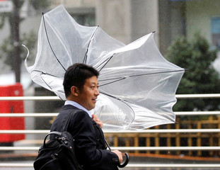 A man using an umbrella struggles against a heavy rain and wind as Typhoon Shanshan approaches Japan's mainland in Tokyo