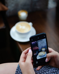The girl is taking pictures of coffee on a smartphone. Hands with the phone close-up pictures of food.