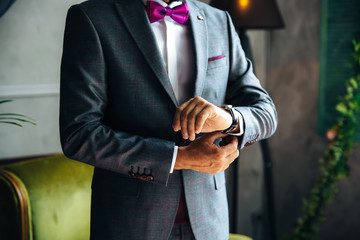 The rundown plan is a cropped frame of a stylish businessman marries today, put on a fashionable suit, wears a white shirt and stylish expensive leather watches, fastens cuff links on his sleeve.