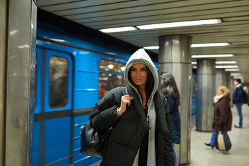 A beautiful happy young woman in a black coat waiting at a subway station with a train in the background.