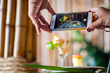 hand of people holding smart phone camera taking shot of food before eating