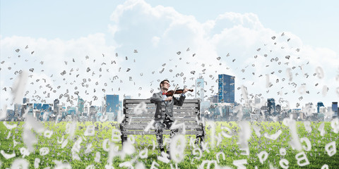 Handsome violinist in park on wooden bench and symbols fly around