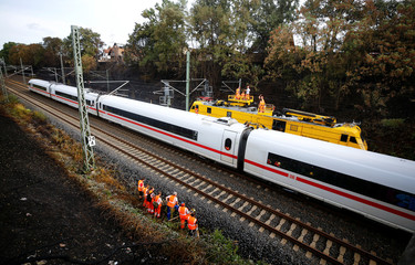 Workers of Deutsche Bahn (German Railways) check the track as an ICE high-speed train passes the site of a fire in Siegburg