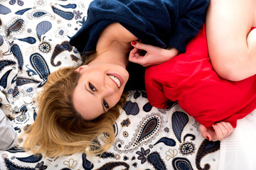 Portrait of a beautiful smiling young woman while lying on a bed and wearing a blue sweater.