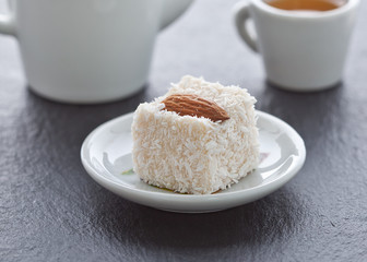 Turkish delight with almonds in coconut chips on a saucer on a slate background.