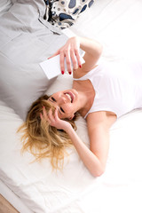 A beautiful smiling young woman lying on a bed in a white tank top and taking a selfie.