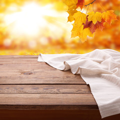Empty wooden table with tablecloth. Napkin close up top view mock up. Autumn rustic background.