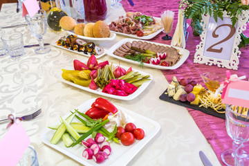 Served tables at the Banquet. Drinks, snacks, delicacies and flowers in the restaurant. A gala event or wedding.