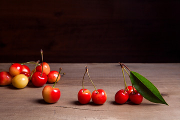Yellow sweet cherry with green leaf on wooden background.