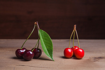 Red and yellow sweet cherry with green leaf on wooden background.