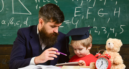 Male kindergarten teacher drawing picture with child. Teacher and pupil in mortarboard, chalkboard on background. Father with beard, teacher teaches son, little boy.