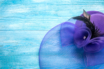 Elegant lady's hat on a blue wooden background