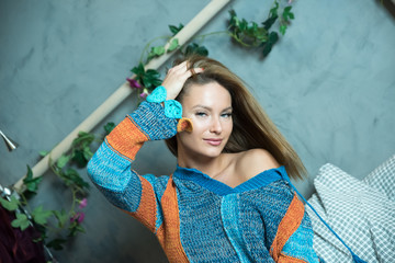 Portrait of a beautiful woman sitting on a bed in a modern apartment and wearing a colourful sweater.